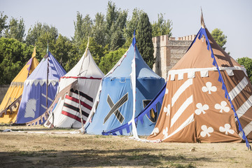 medieval tents next to a field of fair or mourning between warriors