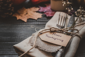 Thanksgiving decoration with cutlery and napkin on the wooden table, close up