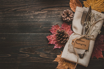 Thanksgiving decoration with cutlery and napkin on the wooden table, top view. Copy space