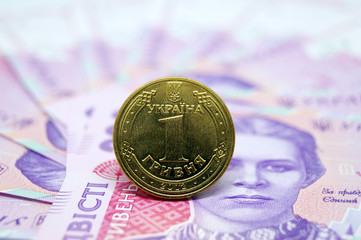 The coin is one hryvnia against the background of paper banknotes of the Ukrainian currency.