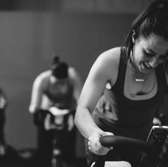Young, happy woman enjoying working hard during spin cycle class