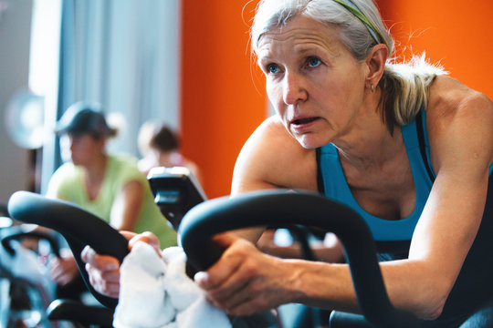 Older caucasian woman working hard during spin cycle class