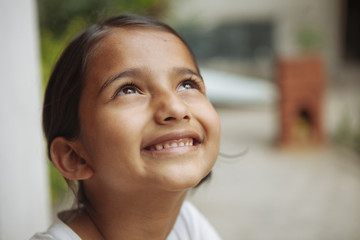 A young south asian girl smiling and looking up.