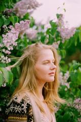 Beautiful blonde woman among lilac