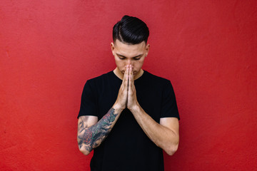 Man with tattoos prayer against a red wall