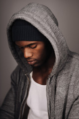 Close up shot of young man in hooded shirt looking down