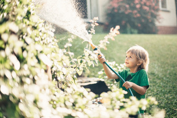 Young beautiful smiling boy playing in the garden with water