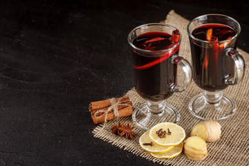 Mulled wine banner. Glasses with hot red wine and spices on dark background. Modern dark mood style.