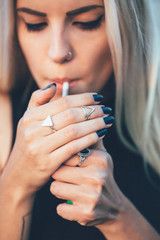 Close up of hip young woman lighting cigarette