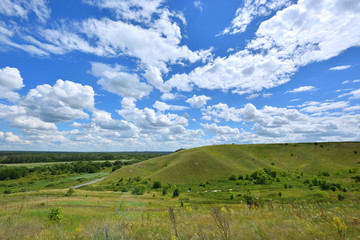 Beautiful landscape with a green hill and a blue sky with clouds