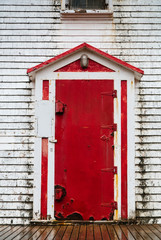 Old red painted door on side of white wood house