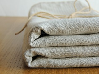 Soft handmade waffle linen cotton towels, kitchen towels, hand towels, bath towels tied with twine on brown wooden background. Gift. Food photo props.