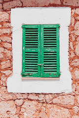 Window with colorful green wooden shutters