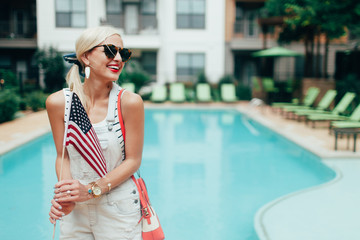 A young blonde woman holding an american flag