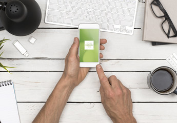 Top View Mockup of User's Hands Holding Smartphone at Desk 1