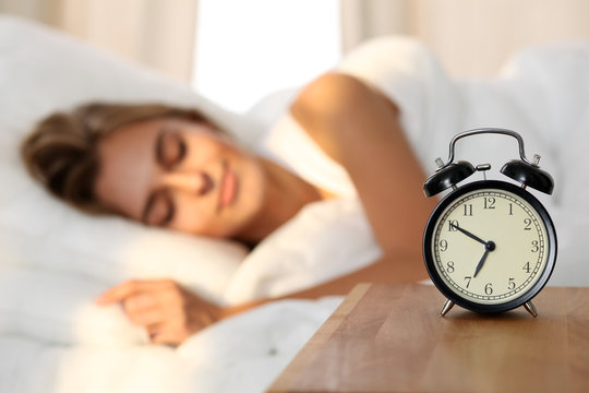 Beautiful young woman sleeping and smiling while lying in bed comfortably and blissfully on the background of alarm clock is going to ring. Sunbeam dawn  on her face.