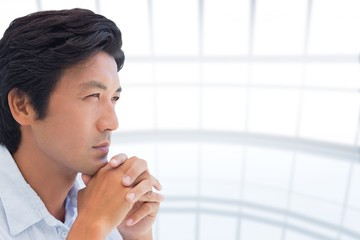 Composite image of thinking man with hands together