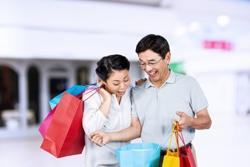 Composite image of older asian couple with shopping bags