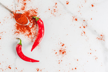 Raw fresh organic and dried ground chili pepper on white marble background top view copy space