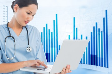 Composite image of concentrated surgeon using a laptop in