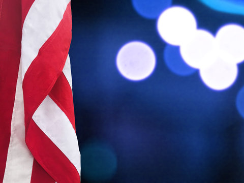 Patriotic Hanging American Flag and Blue Bokeh Lights Background