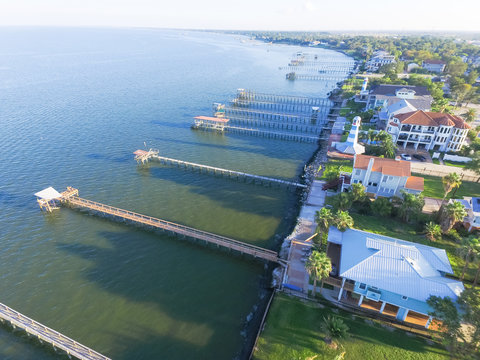 Aerial view three-story waterfront vacation home with fishing piers stretching out over the Galveston Bay in Kemah city, Texas, USA. Bird eye view of Kemah Lighthouse District at sunset.