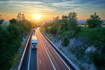 Fotobehang - Three trucks driving on the highway in a rural landscape at sunset. View from above.