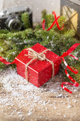 Red present box candle and retro camera with snow Christmas composition