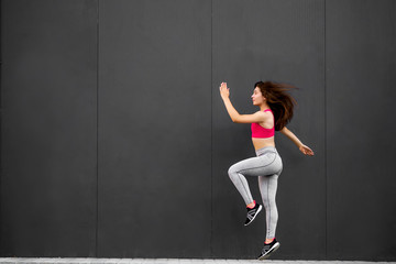 Sport fitness girl in fashion sportswear jumping in the street, on gray wall background ,outdoor sports. Urban style.