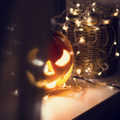 Halloween pumpkin with candle on window. Symbol of halloween.