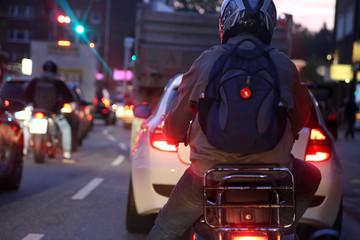 Rollerfahrer und Autofahrer warten im Berufsverkehr morgens