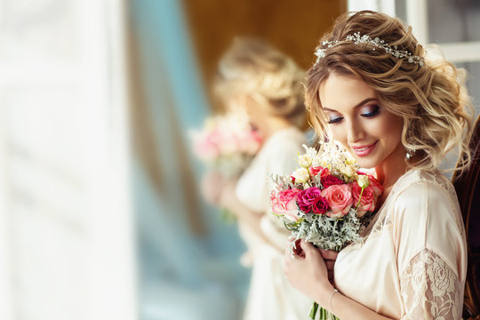 Portrait of a beautiful bride with a wedding bouquet. Blonde girl with curly hair and fashion makeup.