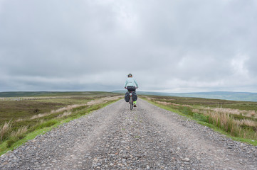 Female cyclist traveling across Northumberland moorland on the UK Coast to Coast cycle route