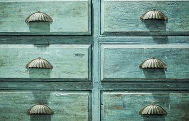 Close up of primitive wooden apothecary or catalog cabinet with partially open drawers - storage and sorting concept or just retro background