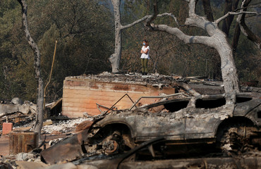 Pamela Garibaldi looks over burned remains of her parents home destroyed by wildfire in Napa, California