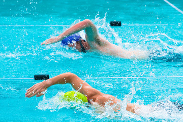 male swimmers competing in freestyle stroke
