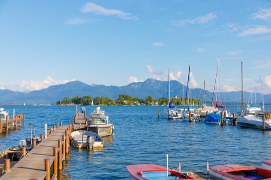 Boats at jetty at Seebruck with Fraueninsel at Lake Chiemsee, Bavaria on a sunny summer day