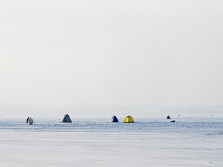 Ice anglers on the lake ice in the cold winter day