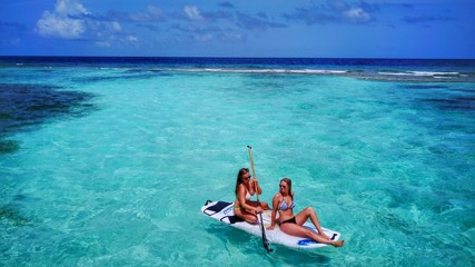 P02095 Aerial flying drone view of Maldives white sandy beach 2 people young woman relaxing on paddleboard on sunny tropical paradise island with aqua blue sky sea water ocean 4k