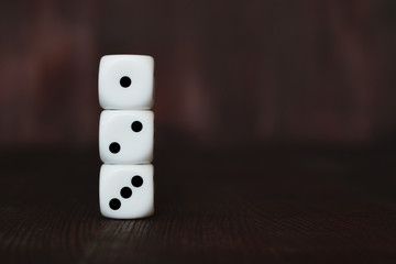 Three white plastic dices on each other on brown wooden board background. Six sides cube with black dots. Start number 123. Wall mural