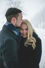 Glückliches Paar in Winterlandschaft gehen mit Wintermantel spazieren