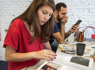Young woman and man sitting in a cafe relaxing. A woman looks at magazines, and a man with a mobile phone.