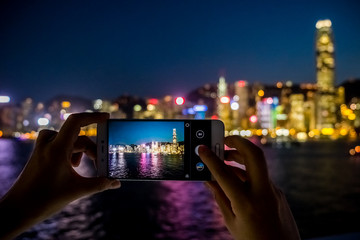 Woman using her Mobile Phone to take photo of city view, twilight Background