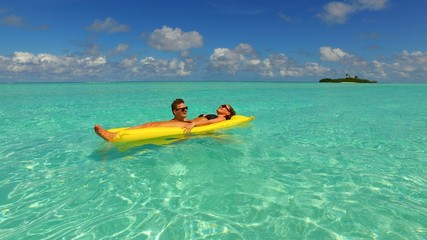 P02917 4k Maldives white sandy beach 2 people young couple man woman floating on airbed inflatable mattress swimming splashing on sunny tropical paradise island with aqua blue sky sea water ocean