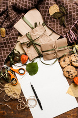 Autumn background of preparing presents. Top view picture of small wrapped gifts with chocolate cookies, scissor and bands, clean paper with pen laying on wooden table with plaid