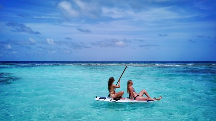 P02108 Aerial flying drone view of Maldives white sandy beach 2 people young woman relaxing on paddleboard on sunny tropical paradise island with aqua blue sky sea water ocean 4k