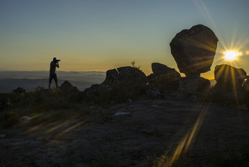 Silhouette of a photographer shooting sun rising above the mountain