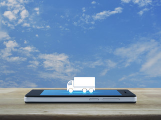 Truck flat icon on modern smart phone screen on wooden table over blue sky with white clouds, Business transportation service concept