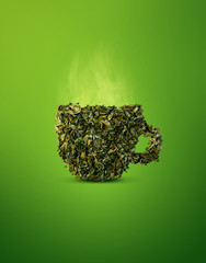 Creative green tea leaves collage. Green tea leaves in shape of cup with warm smoke on green background. Graphic design postproduction for advertisement.