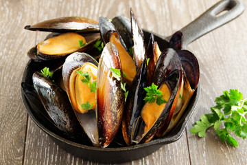 Mussels fried with garlic in a frying pan.